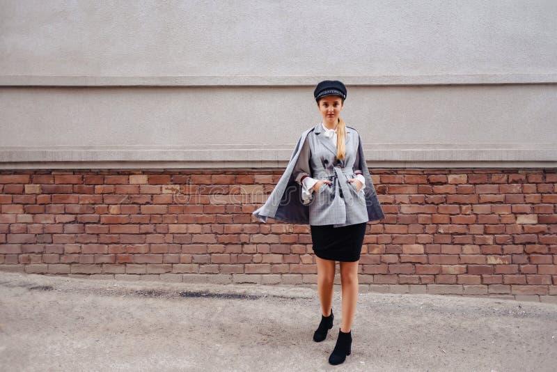 Uma menina bonito, bonita em um terno ? moda anda em torno da cidade e das poses foto de stock royalty free