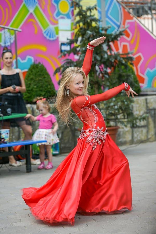 Uma menina bonito em um terno vermelho está dançando na rua r O bebê aprende a dança Dança da mostra ao imagens de stock royalty free