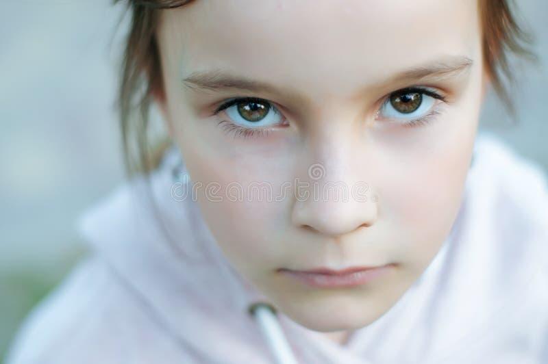 Uma menina bonito pequena com cabelo longo está sentando-se em um parque seriamente triste imagens de stock royalty free