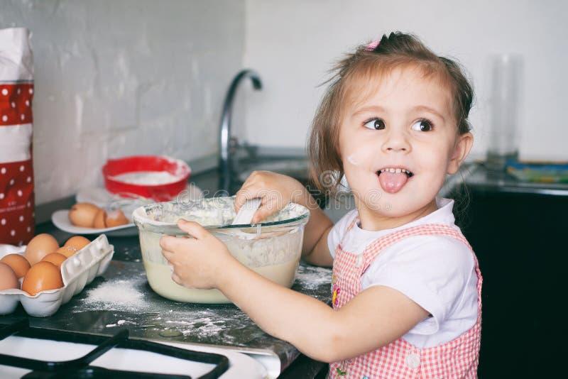 Uma menina bonito pequena que prepara a massa na cozinha em casa fotografia de stock royalty free