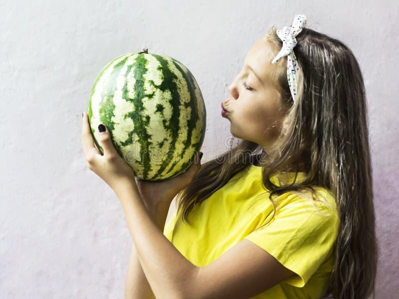 Uma menina bonito que guarda uma melancia madura imagens de stock