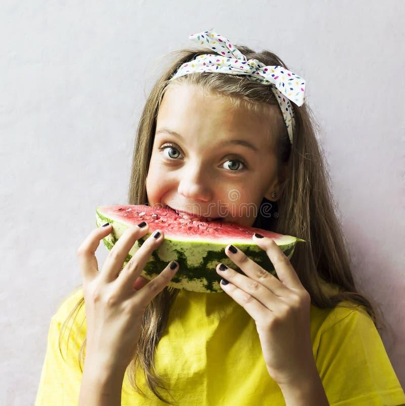 Uma menina bonito que guarda uma melancia madura imagens de stock royalty free