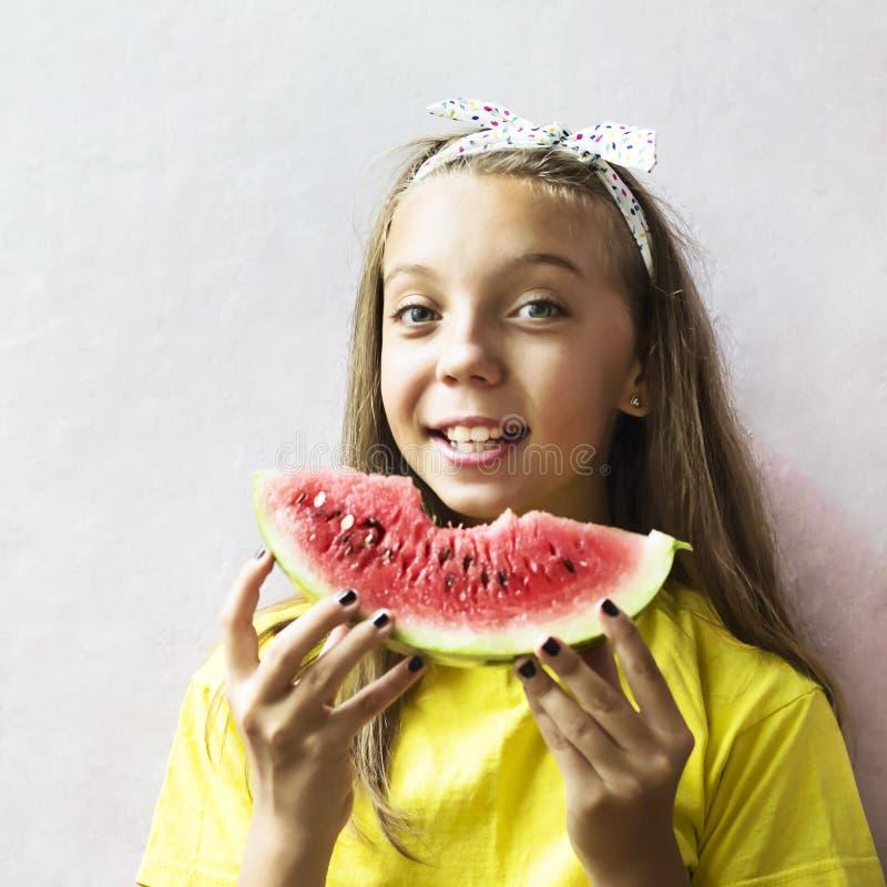 Uma menina bonito que guarda uma melancia madura fotografia de stock royalty free