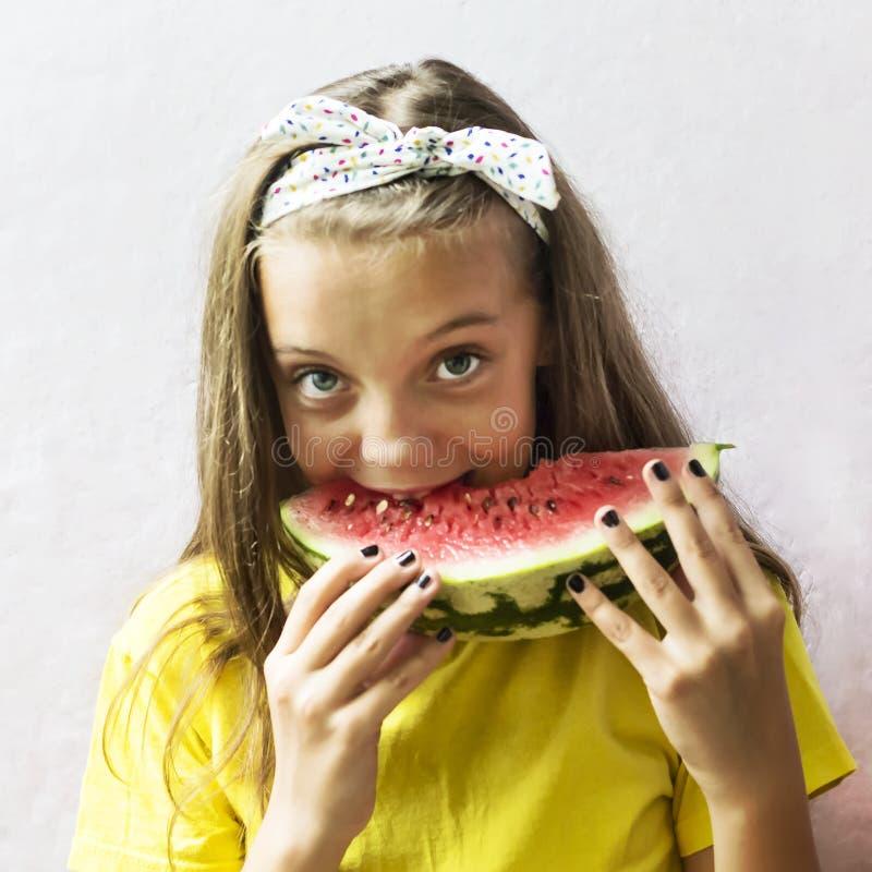 Uma menina bonito que guarda uma melancia madura fotos de stock royalty free
