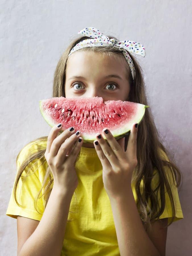 Uma menina bonito que guarda uma melancia madura imagem de stock royalty free