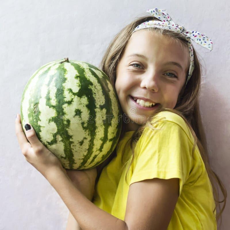 Uma menina bonito que guarda uma melancia madura imagem de stock