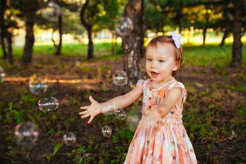 Uma menina bonito que joga com bolhas de sabão no parque imagens de stock royalty free