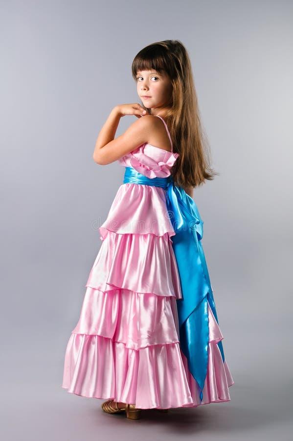 Uma menina bonito que levanta em um vestido da cor-de-rosa do baile de finalistas no estúdio imagens de stock