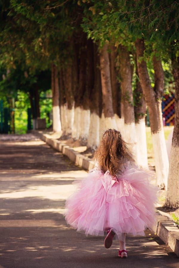 Uma menina borrada que corre no jardim no por do sol do verão me imagens de stock royalty free