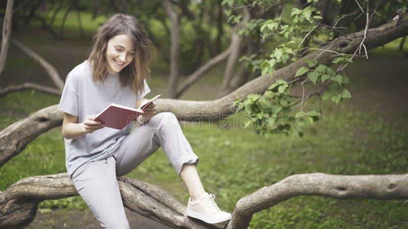 Uma menina branca moreno de riso está lendo um livro no parque imagens de stock
