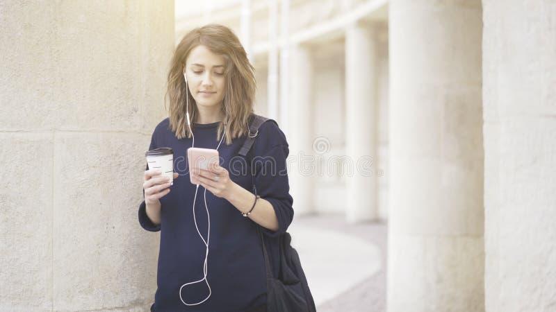 Uma menina branca moreno de sorriso está escutando a música fora fotos de stock