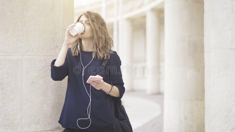 Uma menina branca moreno de sorriso está escutando a música fora imagem de stock royalty free