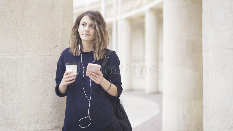 Uma menina branca moreno está escutando a música fora fotografia de stock royalty free
