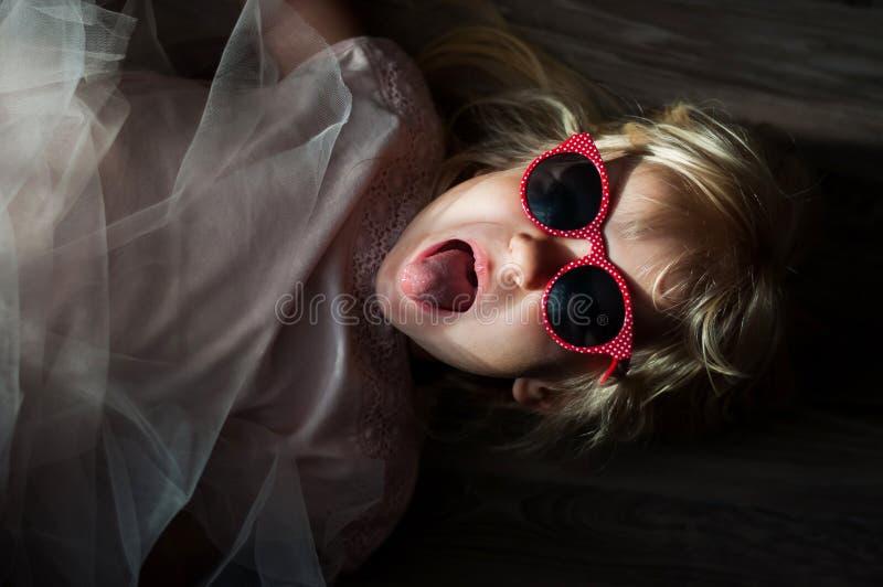 Uma menina caucasiano bonito pequena com óculos de sol encontra-se no assoalho fotografia de stock royalty free