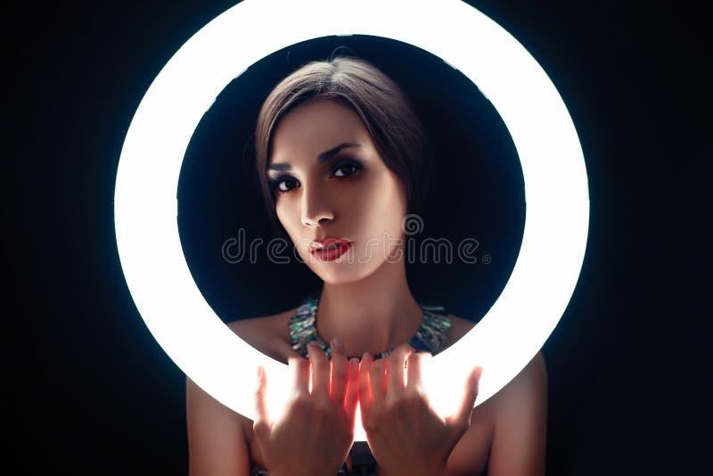 Uma menina caucasiano nova bonita com uma composição bonita olha para fora atrás de uma lâmpada circular para o tiro da foto do r fotografia de stock