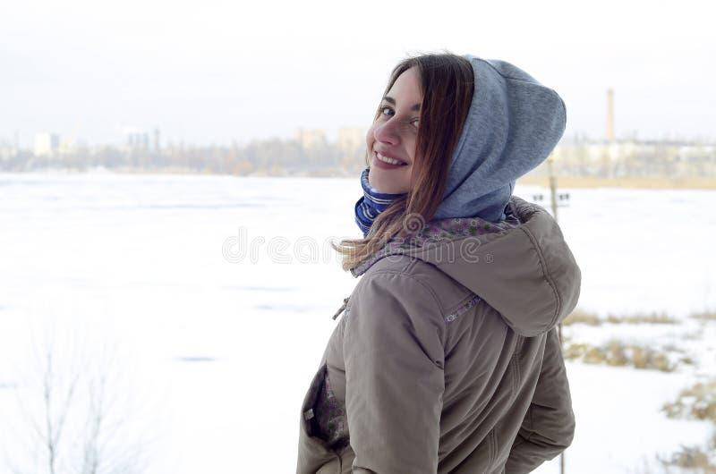 Uma menina caucasiano nova e sorrindo olha em torno da linha do horizonte entre o céu e o lago congelado imagens de stock royalty free