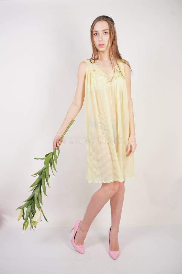 Uma menina caucasiano nova encantador em uma camiseta transparente plissada amarela retro guarda uma flor luxúria do lírio em seu imagem de stock royalty free
