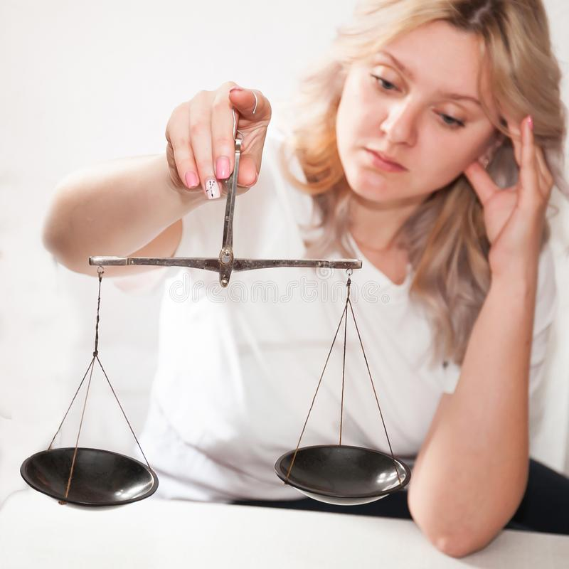 Uma menina com as escalas em suas m?os em um fundo claro toma uma decis?o, pesa o argumento imagem de stock royalty free