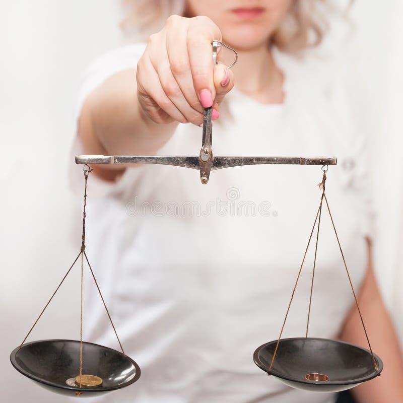 Uma menina com as escalas em suas m?os em um fundo claro toma uma decis?o, pesa o argumento fotografia de stock