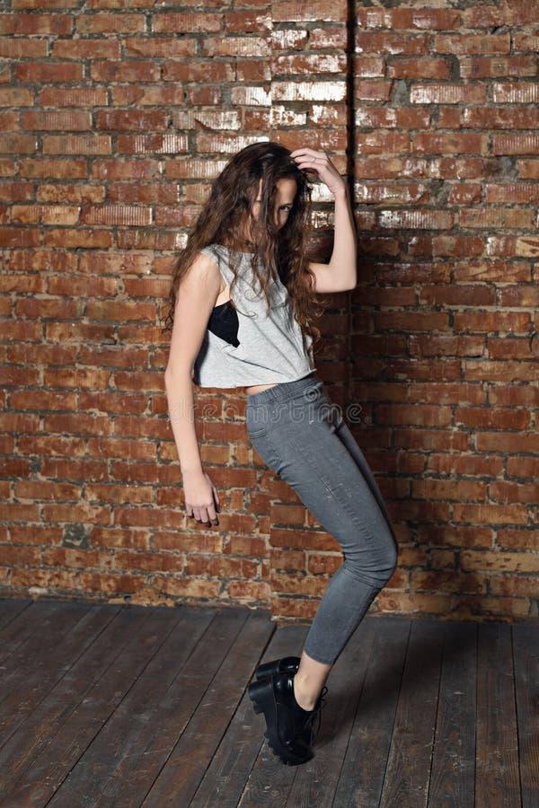 Uma menina com cabelo encaracolado dança em uma adega do armazém do tijolo imagens de stock