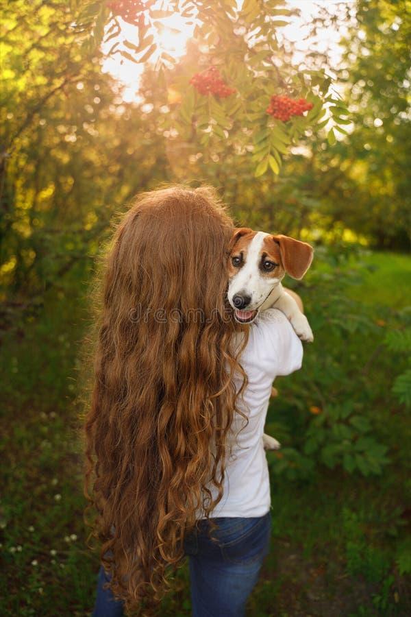 Uma menina com cabelo encaracolado longo está estando com sua parte traseira e está guardando um cachorrinho em seus braços fotos de stock