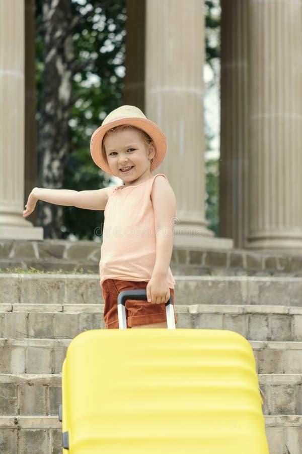 Uma menina com cabelo louro está estando nas etapas com uma mala de viagem amarela grande foto de stock