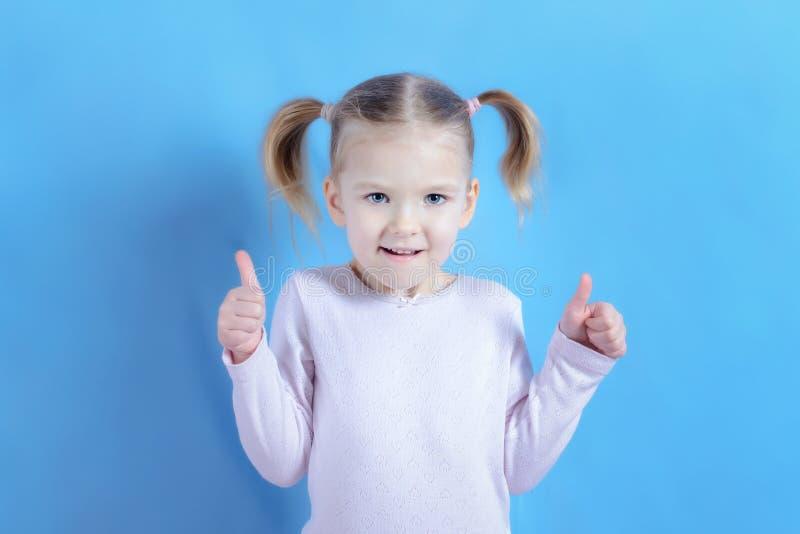 Uma menina com cabelo louro mostra um gesto super com duas mãos Foto de um bebê engraçado em um claro - fundo azul imagem de stock royalty free