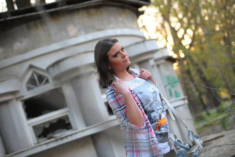 Uma menina com uma camisa colorida e as caneleiras, imaginativamente vê e levanta imagem de stock royalty free