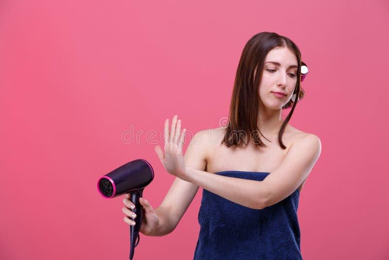 Uma menina, com encrespadores de cabelo e envolvido em uma toalha de banho, guarda um hairdryer e gerencie a cara na aversão dela imagens de stock royalty free