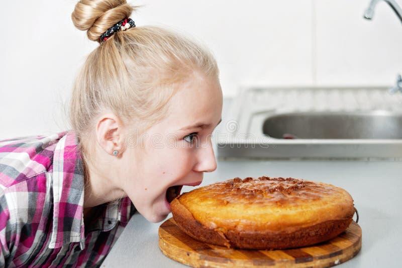 Uma menina com fome com um apetite para morder uma torta deliciosa fotos de stock