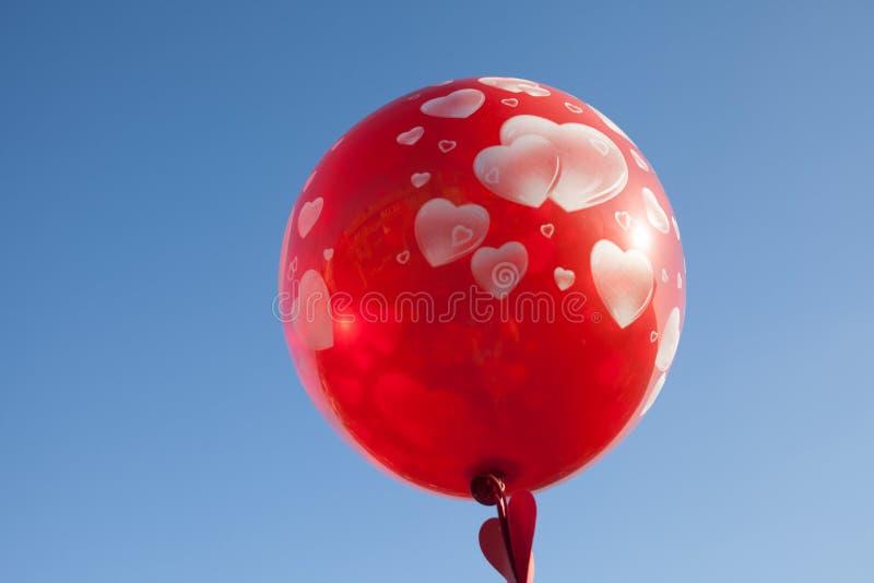 Uma menina com o balão vermelho no céu azul imagem de stock