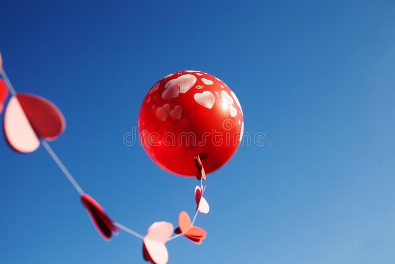 Uma menina com o balão vermelho no céu azul fotos de stock
