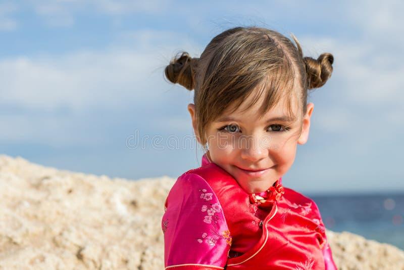 Uma menina com os grandes olhos gerencio-eyed é posta sobre e sorrisos escovados do japanesque sobre um fundo um mar da rocha imagens de stock royalty free