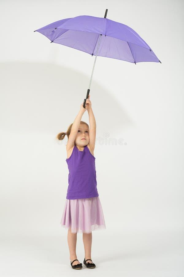 Uma menina com partida do guarda-chuva do roxo do vento foto de stock