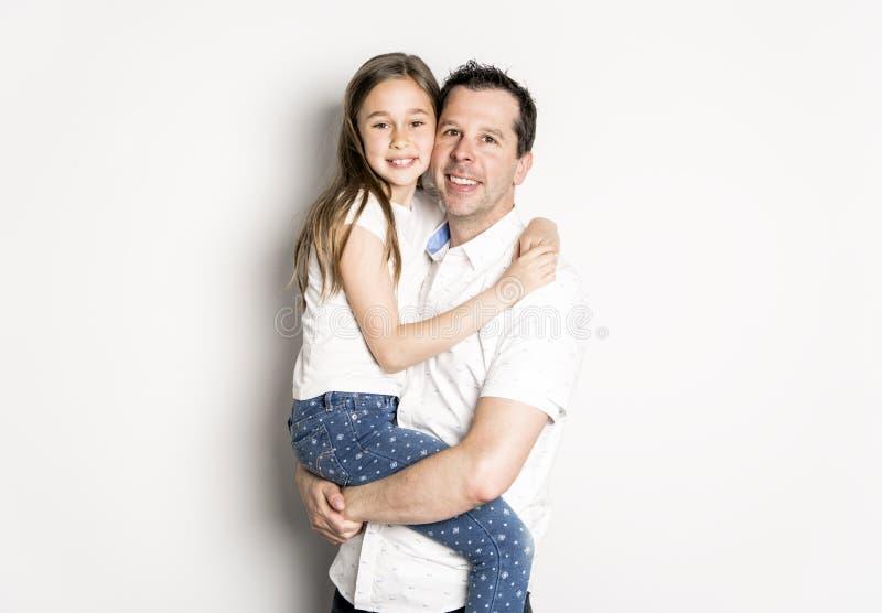 Uma menina com seu pai, isolado no fundo branco imagem de stock