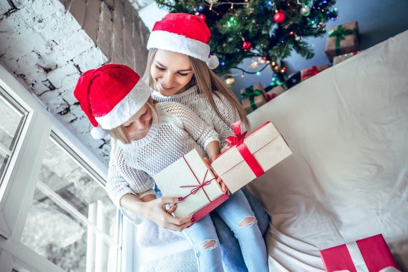 Uma menina com sua mamã abre um presente de ano novo perto de uma árvore de Natal festiva foto de stock royalty free
