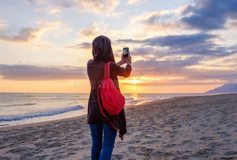 Uma menina com trouxa toma a foto um por do sol em uma c?mera do telefone celular na praia, praia de Patara, Turquia imagens de stock royalty free