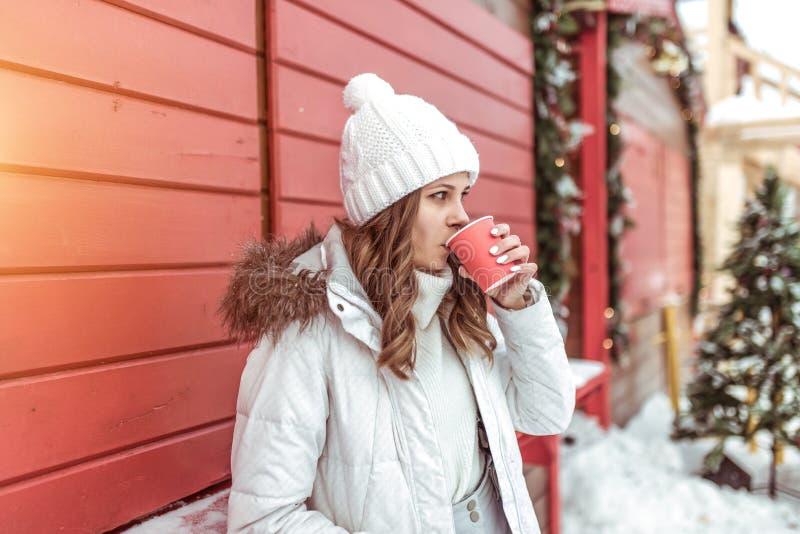 Uma menina com um café do copo bebe uma bebida, suportes na construção de madeira vermelha Em um revestimento e em um chapéu morn fotos de stock