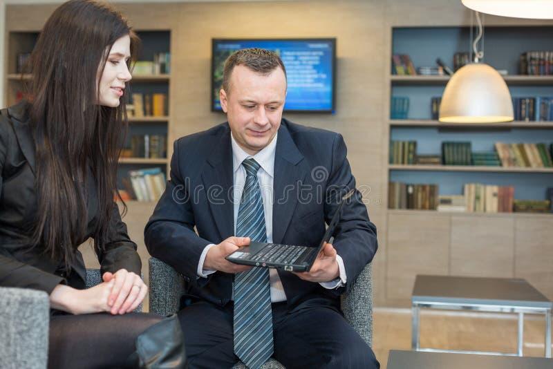 Uma menina com um homem que senta-se com caderno fotografia de stock royalty free