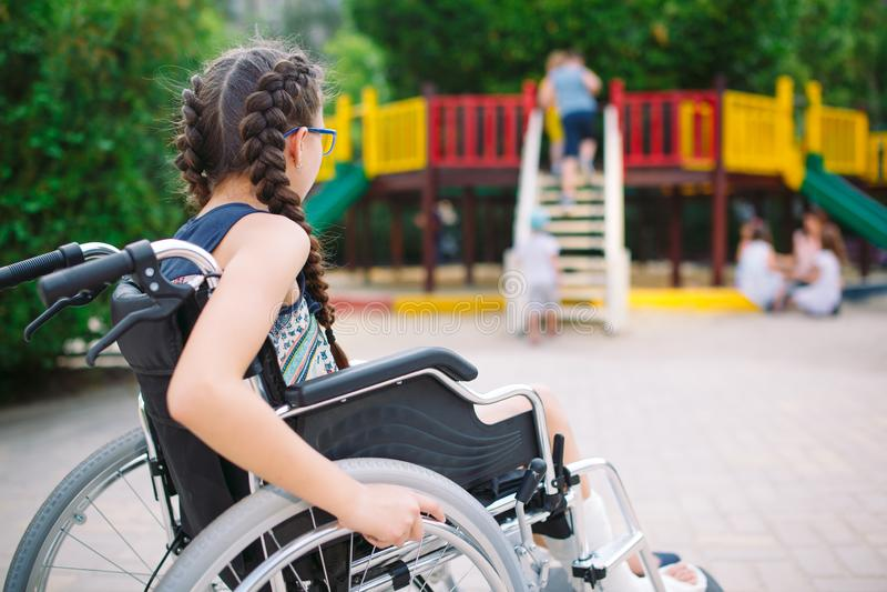Uma menina com um p? quebrado senta-se em uma cadeira de rodas na frente do campo de jogos imagens de stock