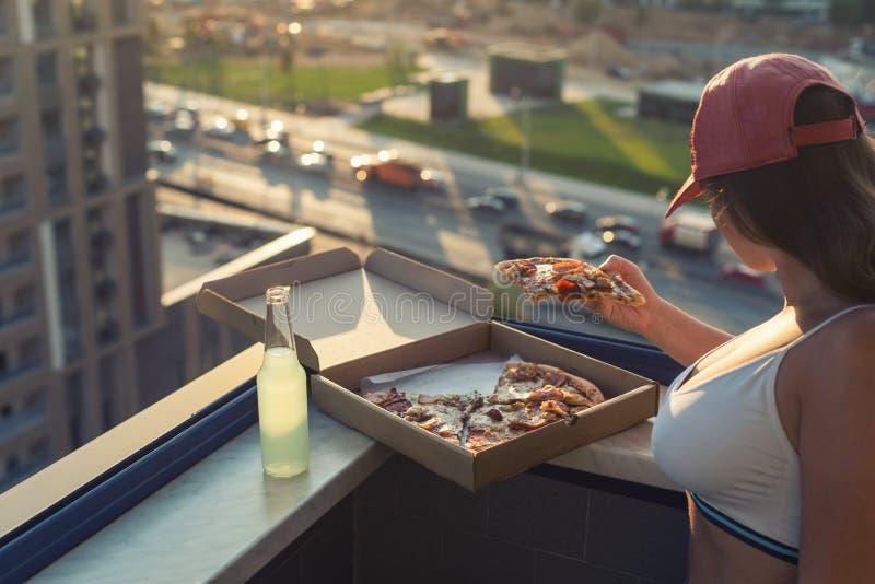 Uma menina com um peito bonito em um terno dos esportes está indo comer a pizza e beber o mojito no fundo da cidade do por do sol foto de stock