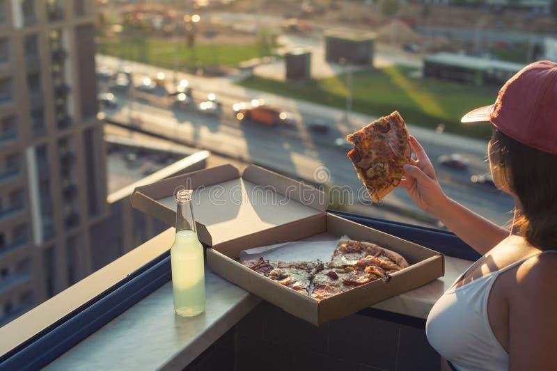 Uma menina com um peito bonito em um terno dos esportes guarda uma parte de pizza grande em sua mão imagens de stock