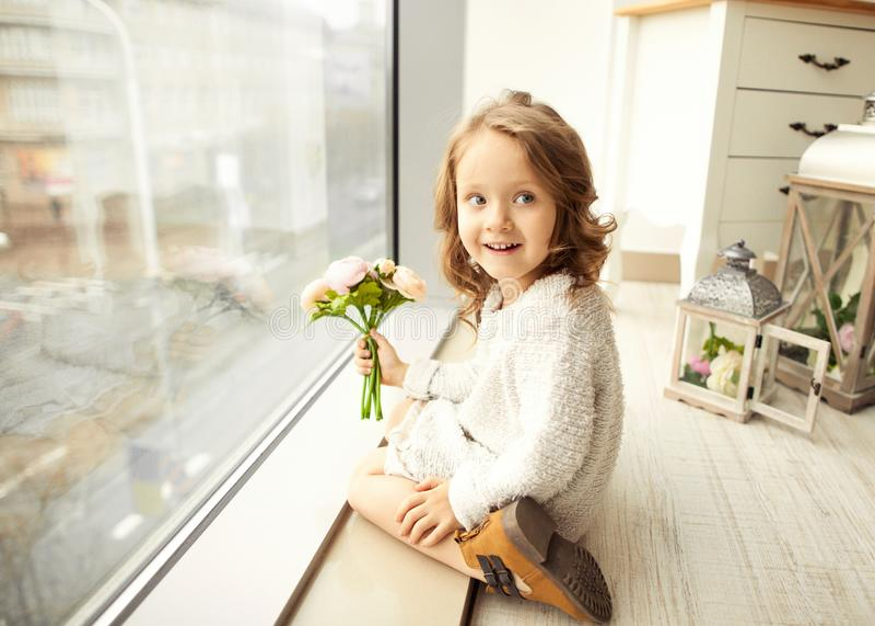 Uma menina com um ramalhete das flores em seu dia do ` s da mãe senta-se imagem de stock royalty free