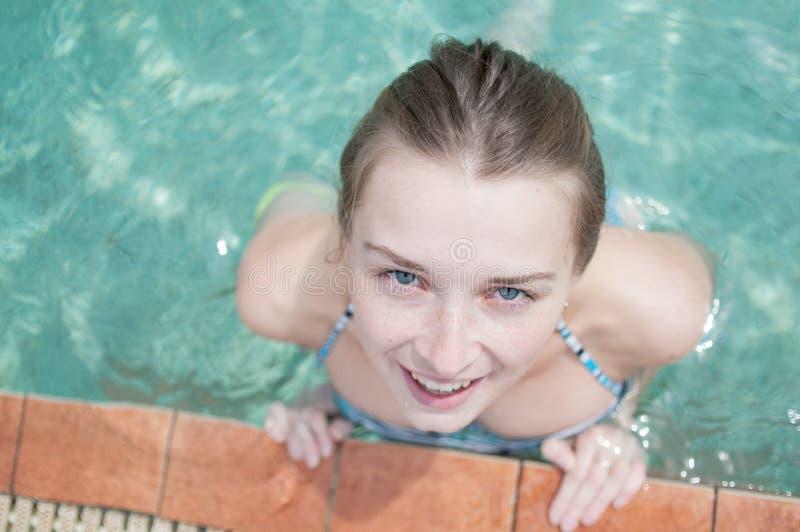 Uma menina com um sorriso bonito em uma piscina em um roupa de banho mulher no vestido do verão que relaxa na ideia de madeira da imagens de stock royalty free