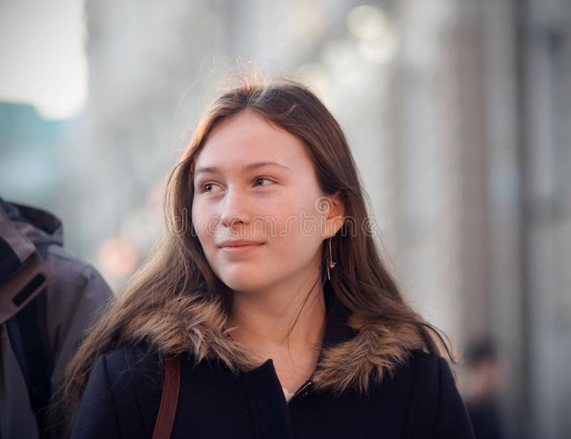 Uma menina com um sorriso que olha um transeunte imagens de stock