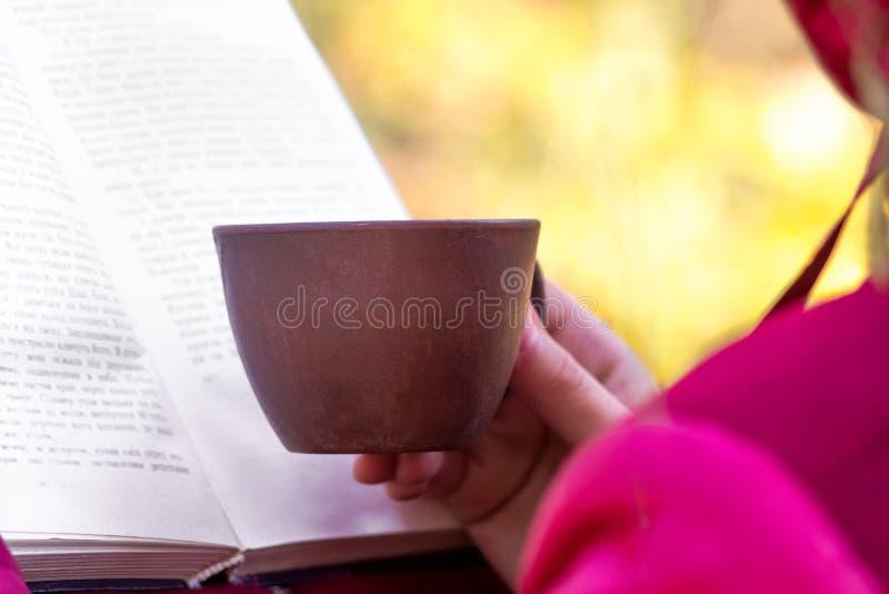 Uma menina com uma xícara de café lê um livro no nature_ foto de stock