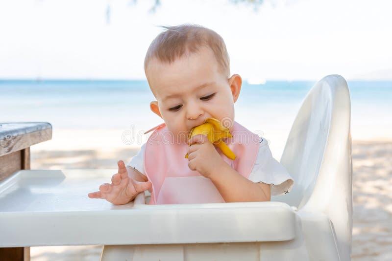 Uma menina come uma banana deliciosa em um Sandy Beach tropical Vista para baixo O bebê encontra o alimento O desenvolvimento da  fotografia de stock royalty free