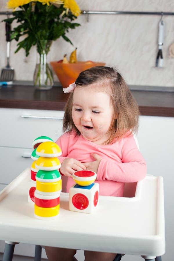 Uma menina da criança de 2 anos com jogos longos do cabelo com uma construção do desenhista em casa, constrói torres, exulta em s fotografia de stock