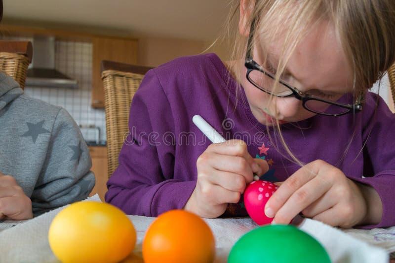 Uma menina da criança de 7 anos está pintando um ovo pontilhado vermelho para easter imagem de stock