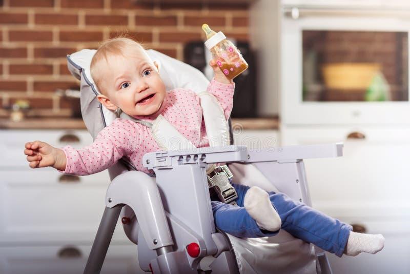 Uma menina da criança do ano senta-se na cadeira alta do bebê com a garrafa de alimentação em sua mão fotografia de stock